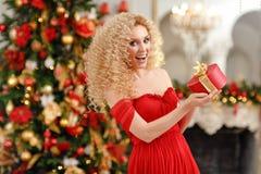 Den lockiga blonda flickan i en röd klänning som rymmer en gåva och, är surprien Royaltyfri Bild