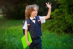 Den lockiga blonda studenten går till skolan royaltyfria foton