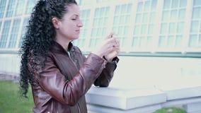 Den lockiga brunetten tar videoen med telefonen stock video