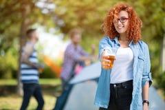 Den lockiga flickan erbjuder ett exponeringsglas av öl Arkivfoton
