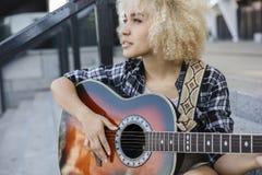 Den lockiga flickan gör kreativitet, henne spelar gitarren på gatan arkivbilder