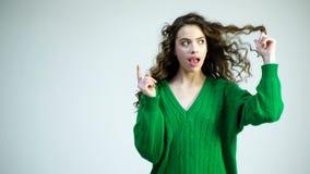 Den lockiga flickan i en grön tröja med hänglsen slår in hennes hår på hennes finger Retro flicka med stilfull makeup och hår i p stock video