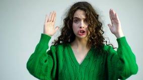 Den lockiga flickan i en grön tröja med hänglsen stänger hennes framsida med henne händer och visar olika sinnesrörelser Parisisk arkivfilmer
