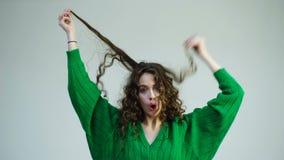 Den lockiga flickan med hänglsen i en gräsplantröja drar hennes hår av på en vit bakgrund Begreppet av håromsorg parisian lager videofilmer