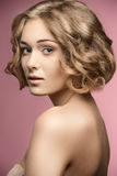 Den lockiga kvinnan med guppar hår-snittet arkivbild
