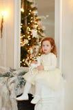 Den lockiga lilla flickan behandla som ett barn sammanträde på spiselkranens på jul Arkivfoton