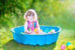 Den lockiga litet barnflickan som spelar will, klumpa ihop sig i trädgården Fotografering för Bildbyråer