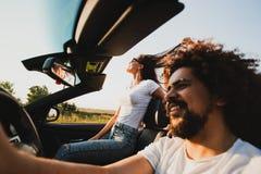Den lockiga mörker-haired unga mannen som sitter på hjulet av en svart cabriolet och en härlig kvinna, sitter bredvid honom på a royaltyfri foto