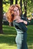 Den lockiga unga kvinnan i klänning poserar bland träd Arkivfoton