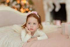 Den lockigt lilla flickan behandla som ett barn att ligga på sängen och ledset på jul Royaltyfria Bilder