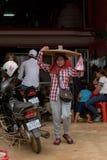 Den lokala gatabutiksinnehavaren som säljer kryddig chilipeppar, beskjuter att gå med produkten på huvudet Royaltyfri Foto