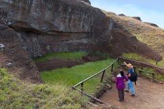 Den lokala handboken utbildar en besökare på de oavslutade Moai statyerna Royaltyfri Foto