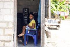 Den lokala unga kvinnan som vårdar henne, behandla som ett barn sammanträde på en blå stol Arkivbilder