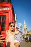 Den London loppmodern och behandla som ett barn turisten vid Big Ben och det röda telefonbåset Arkivfoto