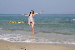Den Longhaired brunetten i svart bikini tycker om sommar på stranden royaltyfria foton