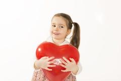 Den älskvärda lilla flickan som spelar med röd hjärta, formade ballongen Arkivbild