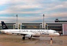 Den LUFTHANSA flygbussen A319-100 landar på den Flughafen Munich flygplatsen MUC, den andra mest upptagna flygplatsen i Tyskland Royaltyfri Fotografi