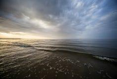 Den lugna Östersjön och den färgrika solnedgånghimlen Arkivfoton