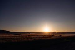 Den lugna aftonsolen exponerar färgrika fält och kullar Arkivfoto