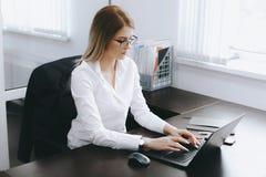 Den lugna allvarliga unga attraktiva blonda kvinnan använder bärbara datorn för att arbeta på tabellen i regeringsställning arkivbild
