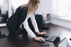 Den lugna allvarliga unga attraktiva blonda kvinnan använder bärbara datorn för att arbeta på tabellen i regeringsställning arkivbilder