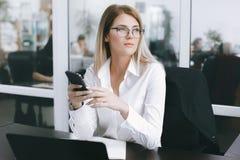 Den lugna allvarliga unga attraktiva blondinen använder telefonen, medan arbeta på tabellen i regeringsställning royaltyfri foto