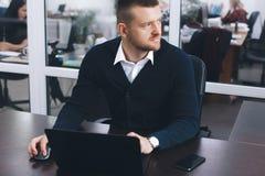 Den lugna allvarliga unga mannen använder bärbara datorn för att arbeta på tabellen i regeringsställning arkivfoto