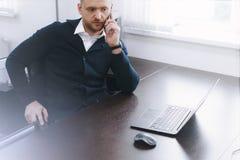 Den lugna allvarliga unga mannen använder telefonen, medan arbeta på tabellen i regeringsställning fotografering för bildbyråer