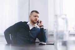Den lugna allvarliga unga mannen använder telefonen, medan arbeta på tabellen i regeringsställning royaltyfri foto
