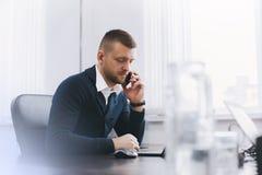 Den lugna allvarliga unga mannen använder telefonen, medan arbeta på tabellen i regeringsställning arkivbild