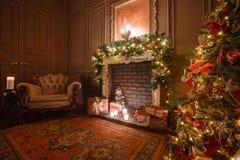 Den lugna bilden av det inre klassiska trädet för det nya året dekorerade i ett rum med spisen Royaltyfria Foton