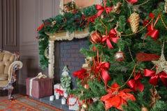 Den lugna bilden av det inre klassiska trädet för det nya året dekorerade i ett rum med spisen Arkivfoton