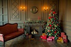 Den lugna bilden av det inre klassiska trädet för det nya året dekorerade i ett rum med spisen Fotografering för Bildbyråer