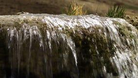 Den lugna mineraliska vattenfallet som strömmar över travertinen, vaggar arkivfilmer