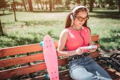 Den lugna och fridsamma flickan sitter på den utvändiga bänken och ser hennes musikspelare Hon bär roliga exponeringsglas Arkivfoto