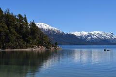 Den lugna sjön reflekterade berg med snö royaltyfri fotografi