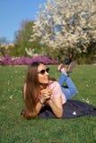 Den lyckade affärskvinnan som ligger på gräs som tycker om fri tid för fritid i, parkerar med att blomstra sakura körsbärsröda tr fotografering för bildbyråer