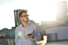 Den lyckade affärsmannen i exponeringsglas står med telefonen i en modern stad Arkivfoto