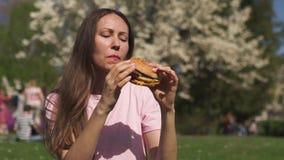 Den lyckade aff?rskvinnan som ?ter snabbmathamburgarecheesburger, tycker om hennes fritid som fri tid i parkerar med att blomstra stock video