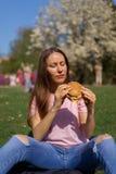 Den lyckade aff?rskvinnan som ?ter snabbmathamburgarecheesburger, tycker om hennes fritid som fri tid i parkerar med att blomstra royaltyfri foto
