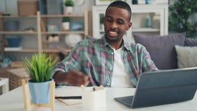 Den lyckade afrikansk amerikanfreelanceren arbetar hemma genom att använda bärbara datorn som sitter på skrivbordet i studion som arkivfilmer
