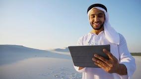 Den lyckade arabiska affärsmannen rymmer i händer och använder minnestavla, s royaltyfri foto