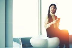 Den lyckade asiatiska affärskvinnan knyter kontakt via apparaten för celltelefonen arkivfoton