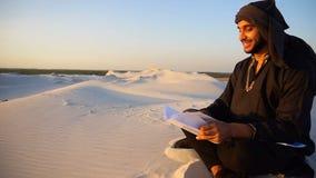 Den lyckade Emirati affärsmannen läser affärsplan och sitter på varm sand i mitt av öknen på sommarafton arkivfilmer