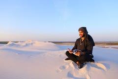 Den lyckade Emirati affärsmannen läser affärsplan och sitter på w Fotografering för Bildbyråer