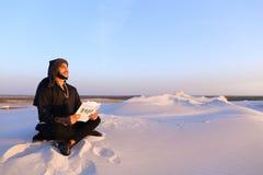 Den lyckade Emirati affärsmannen läser affärsplan och sitter på w Royaltyfri Fotografi