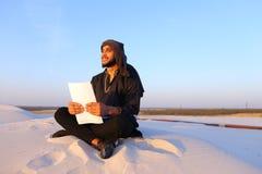 Den lyckade Emirati affärsmannen läser affärsplan och sitter på w Arkivfoton