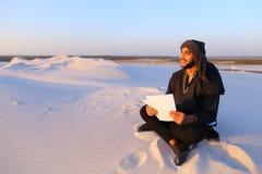 Den lyckade Emirati affärsmannen läser affärsplan och sitter på w Arkivbild