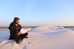 Den lyckade Emirati affärsmannen läser affärsplan och sitter på w Arkivfoto