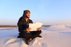 Den lyckade Emirati affärsmannen läser affärsplan och sitter på w Arkivbilder